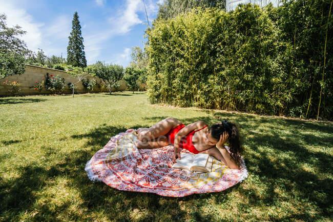 Mujer leyendo en una toalla en el jardín con traje de baño bajo un árbol - foto de stock