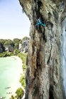 Athletic man rock climbing high above beach on multi pitch route in Tonsai, Thailand — Stock Photo