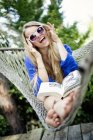 Woman in colorful sunglasses laughing at camera while sitting in hammock and reading book — Stock Photo