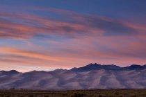 Dunes et montagnes au coucher du soleil — Photo de stock