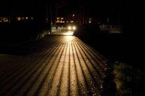 Carro um portão com sombra no asfalto de iluminação — Fotografia de Stock