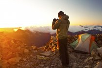 Young male hiker taking picture of sunrise from camp on summit of Frosty Peak in Manning Provincial Park, British Columbia, Canada. — Stock Photo