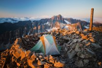 Tienda de set en el pico de la montaña en la cálida luz del sol - foto de stock