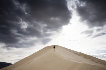Mann auf Sand Düne unter bewölktem Himmel Wandern — Stockfoto