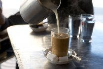 Hot milk pouring in glass of coffee — Stock Photo