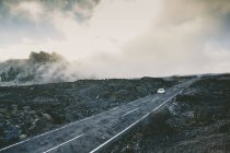 Car travels on a misty road surrounded by volcanic rocks — Stock Photo
