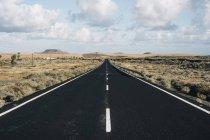 Пряма дорога в середині пустелі з хмарного неба — стокове фото