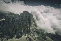 Picos de montanha rochosa rodeados de nuvens — Fotografia de Stock
