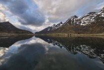 Montañas nevadas con reflejo de cielo nublado en el lago - foto de stock