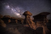 Milky way stars shining in night sky above rock formations — Stock Photo