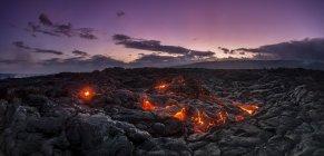 Rotura de lava fresca bajo el cielo púrpura del crepúsculo - foto de stock