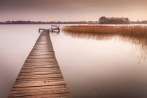 Empty bench at end of jetty, Reeds Lake, Michigan, USA — Stock Photo