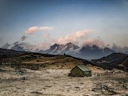 Tent set on hills near snowcapped mountains — Stock Photo