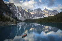 Mountains reflecting in lake with person in canoe — Stock Photo