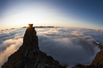 Закат солнца за стойкой рок, окруженный облака — стоковое фото