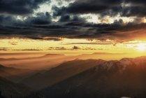 Illuminated sunset sky with clouds above mountain range — Stock Photo