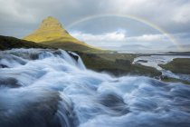 Rainbow over green Kirkjufell mountain with river water flow on foreground — Stock Photo
