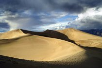 Soleil éclairé des dunes de sable avec une silhouette humaine sous un ciel nuageux bleu — Photo de stock