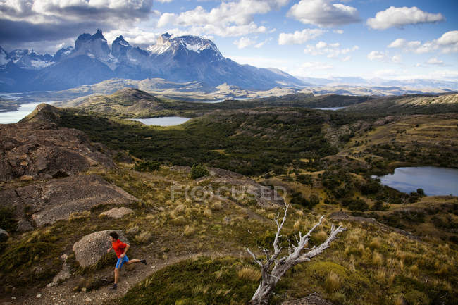 Male adult runner following trail on ridge line with dramatic view in background in Torres Del Paine National Park, Patagonia, Chile. — Stock Photo