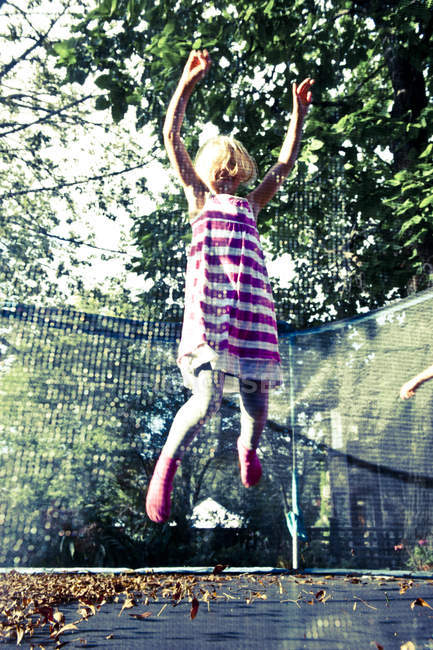 Girl jumping on trampoline, selective focus — Stock Photo