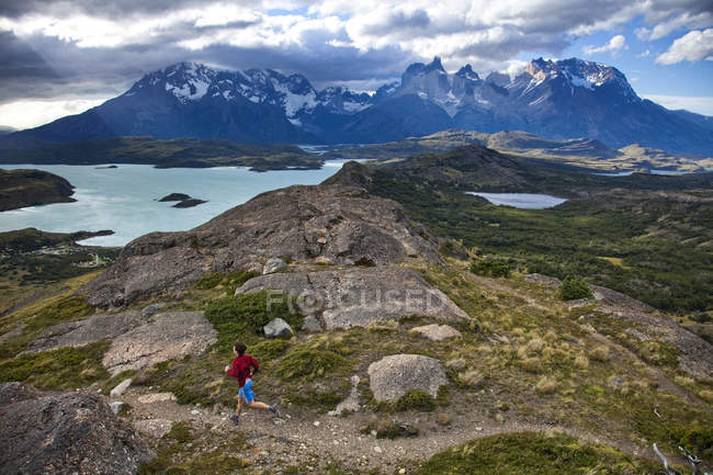 Runner following trail with dramatic view in background — Stock Photo