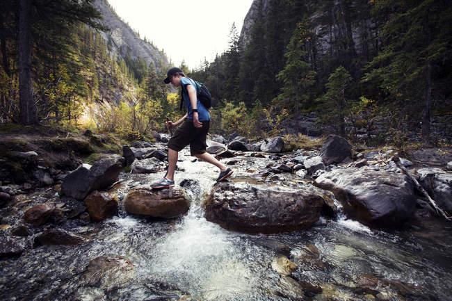 Adolescente attraversa creek esplorando il deserto in montagne rocciose, Alberta, Canada — Foto stock