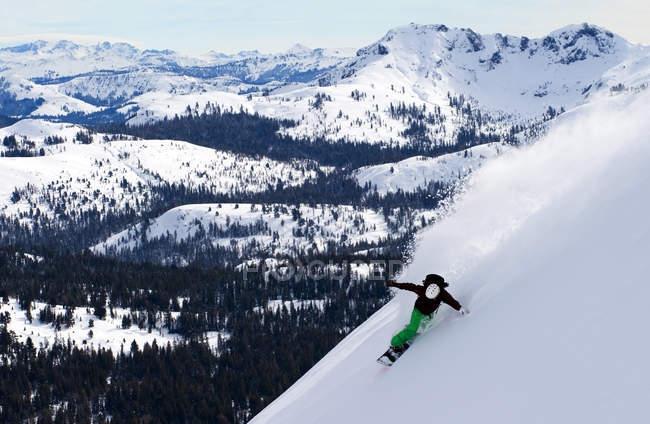 Snowboarder riding huge turn in deep powder on Red Lake Peak near Lake Tahoe, CA — Stock Photo