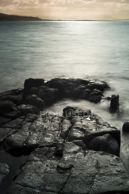 Tir longue exposition de l'eau sur l'estran rocheux — Photo de stock