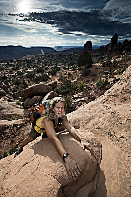 Woman climbing up rock in Arches National Park, Utah — Stock Photo