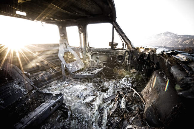 Burned out truck interior at sunset light — Stock Photo