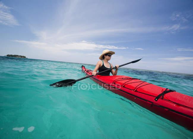 Donna esplorare le acque cristalline dei Caraibi in kayak da mare rosso — Foto stock