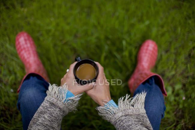 Жіночих рук проведення чашку кави, точки зору — стокове фото
