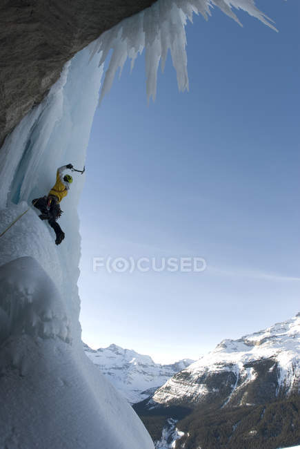 Ice climber swinging at frozen waterfall on Curtain Call Icefield Parkway, Alberta, Canada — Stock Photo
