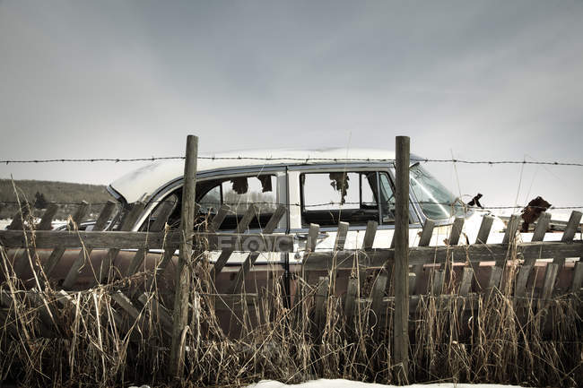 Old car abandoned with smashed windows in farm field near fence, selective focus — Stock Photo