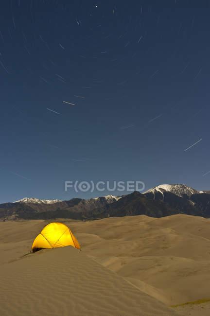 Tente sur des dunes de sable avec des étoiles en mouvement — Photo de stock