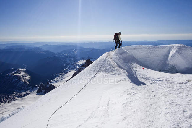 Climber descending Mount Rainier and avoiding crevasse on sunny day — Stock Photo