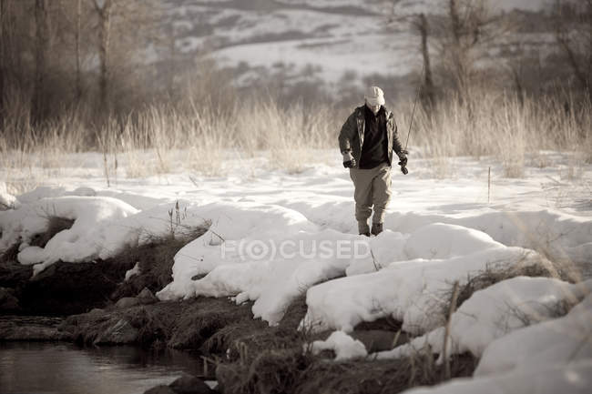 Man walking through snow to fly fish on Utahs Provo River — Stock Photo