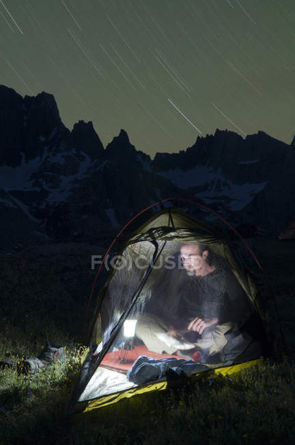 Male hiker reading by lantern in tent at night below Cirque of Towers in Wind River Range, Pinedale, Wyoming — Stock Photo