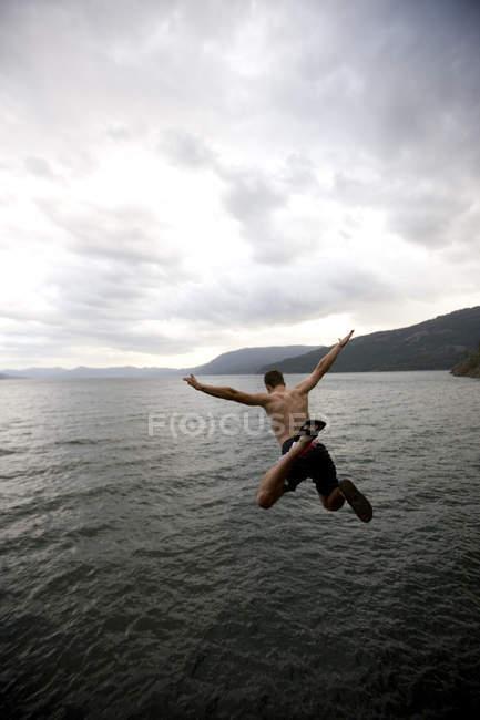 Rear view of man jumping into Lake Pend Oreille, Idaho — Stock Photo