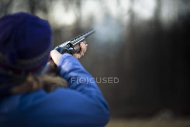 Donna che tiene la volata della canna di fucile fumo dopo essere stato licenziato durante le riprese di tiro al piattello, fuoco selettivo — Foto stock