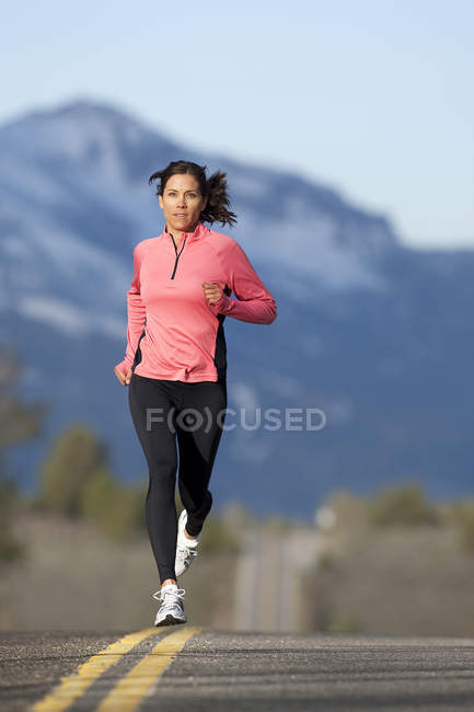 Athletic woman running on mountain road in South Lake Tahoe, California — Stock Photo