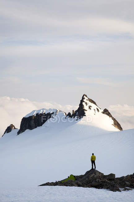Man standing on rock on glacier near small bivy tent while climbing in North Cascades, WA — Stock Photo