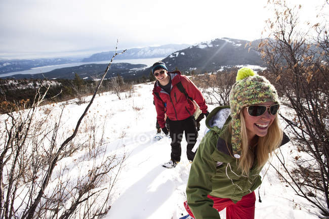 Young couple smiling while snowshoeing on winter day in Sandpoint, Idaho — Stock Photo
