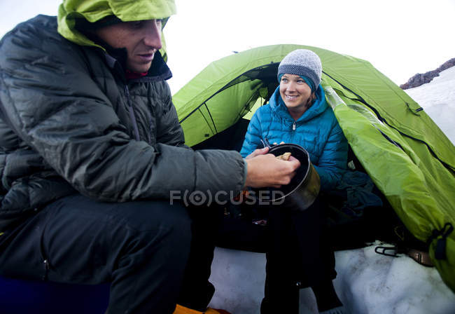 Couple enjoying camping at Camp Muir and eating food before climbing to summit of volcano — Stock Photo