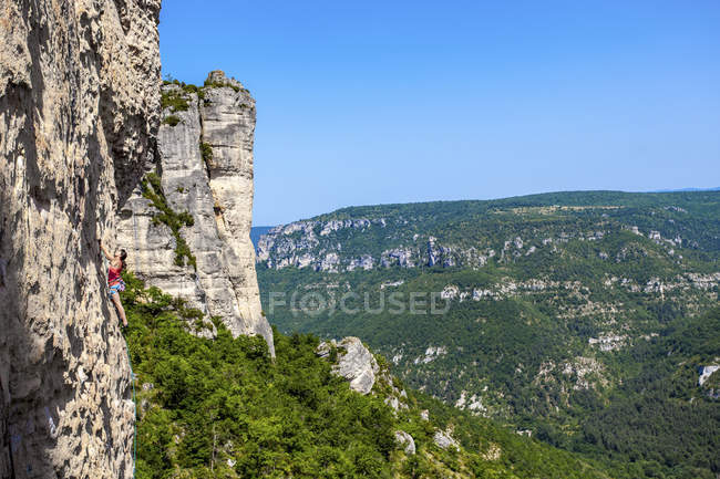 Female climber venturing up on demanding limestone crag above city of Millau, Midi-Pyrnes, France — Stock Photo