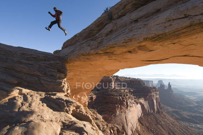 Male hiker jumping down off Mesa Arch in Canyonlands National Park, Moab, Utah — Stock Photo