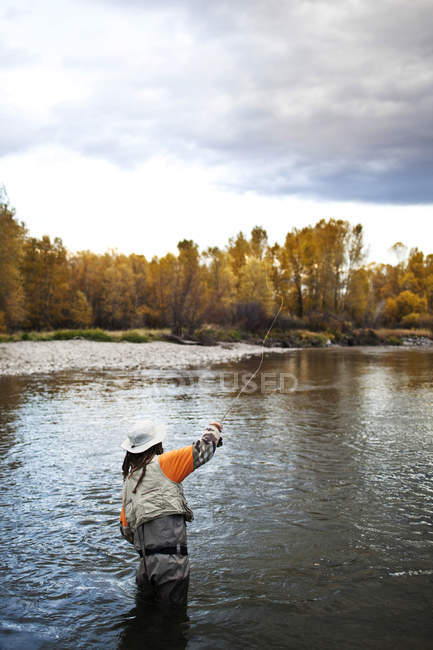 Athletic man fly fishing standing in Yellowstone River with fall colors and snowy mountains in Bozeman, Montana — Stock Photo