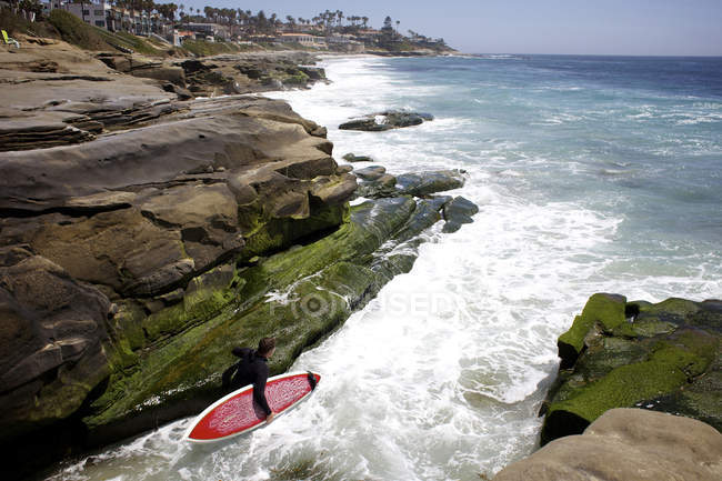 Male surfer between rocks before jumping in water to surfing at Windnsea Beach in La Jolla, CA — Stock Photo