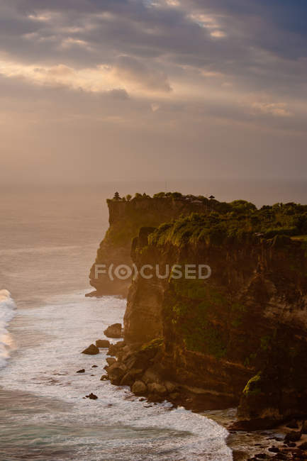 Ocean waves breaking against high tree covered cliffs at sunset — Stock Photo