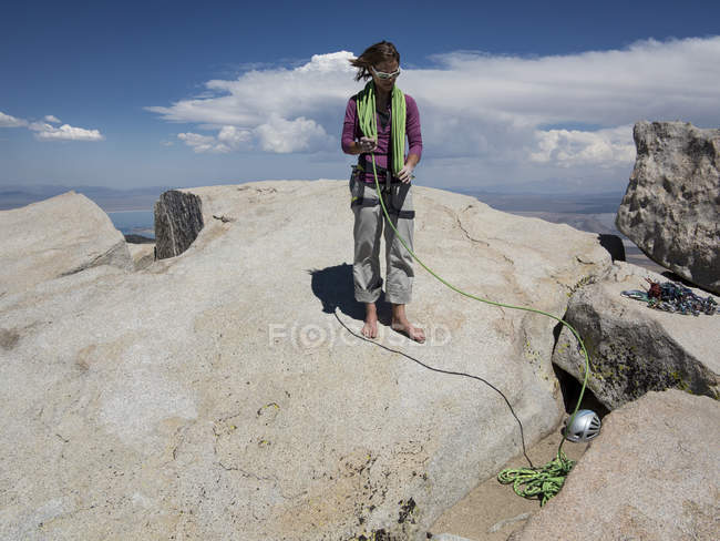 Female rock climber coiling rope after reaching top of Third Pillar of Dana — Stock Photo